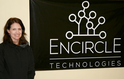 Woman standing next to Encircle Technologies sign