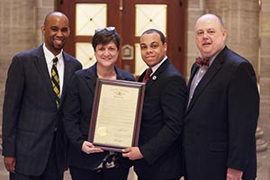 Four people standing together, with the two center people holding a legislative resolution