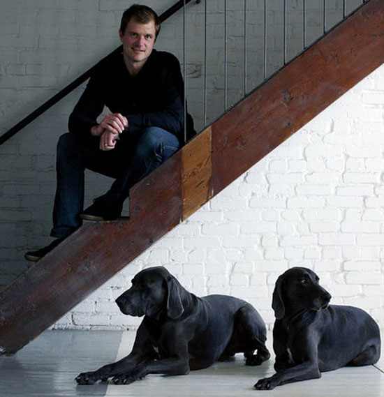 Man sitting on stairs above two dogs
