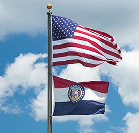 U.S. and Missouri flags with blue sky