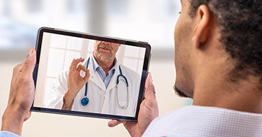 Man using tablet for virtual medical appointment