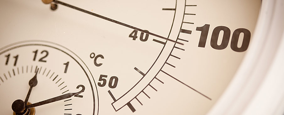 An outdoor thermometer displaying a temperature of 100 degrees