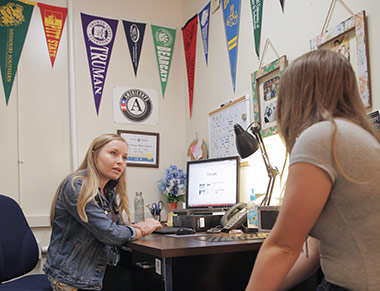 A college adviser assists a high school student.