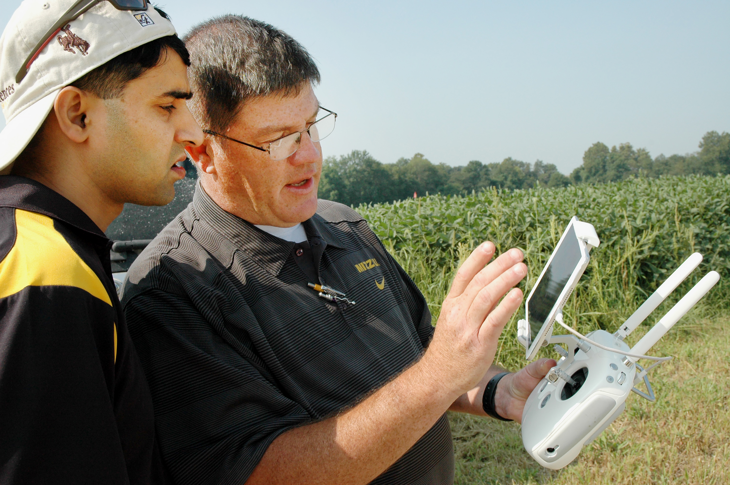 Kent Shannon, right, shows agronomy specialist Dhruba Dhakal how to use a drone to take aerial images of a soybean field in the Missouri Strip Trial Program.