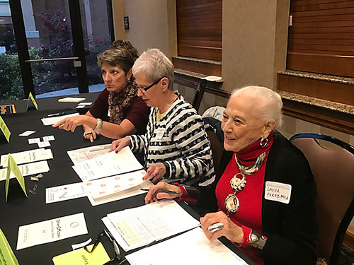 Osher volunteers work a registration table at an event.