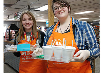 Two girls in aprons providing free samples at a grocery store.