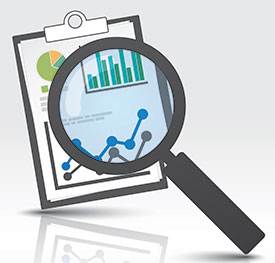 Magnifying glass on top of a research report showing graphs